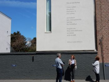 Poems along the wall with a literary scholar